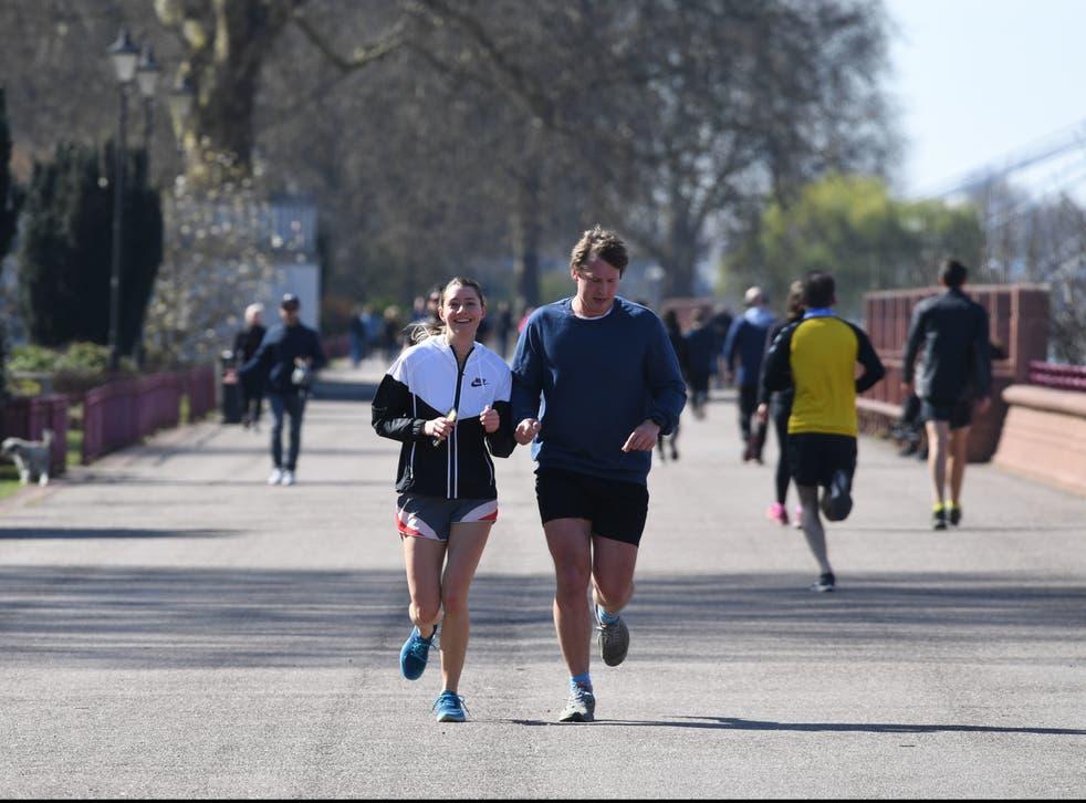 <p>People jogging in Battersea Park, London</p>
