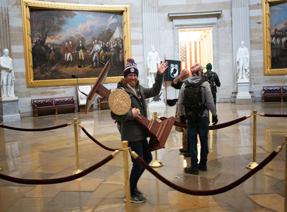 <p>Adam Christian Johnson, 36, who took away a lectern waving to the camera, became one of the most prominent symbols of the Capitol riots</p>