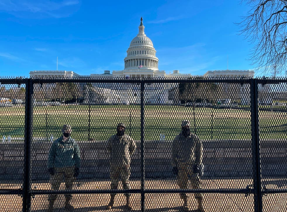 <p>National Guard soldiers guard the grounds of the US Capitol from behind a security fence in Washington, DC</p>