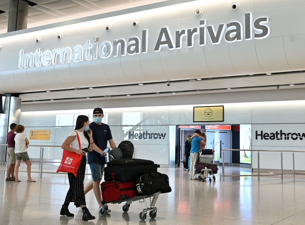 <p>Passengers wearing PPE (personal protective equipment), including a face mask as a precautionary measure against COVID-19, walk through the arrivals hall after landing at at Terminal Two of London Heathrow Airport&nbsp;</p>