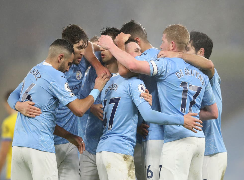 Manchester City players celebrate with a group embrace