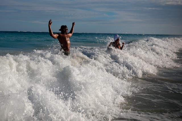 """<p>El turista estadounidense Latron Evans y su compañera Nika, retozando en las aguas del océano en la playa de Tulum, estado de Quintana Roo, México, el lunes 4 de enero de 2021. Evans, un bombero de Mississippi, dijo que estaba impresionado por las medidas de salud debido al nuevo pandemia de coronavirus. """"Están tomando la temperatura cuando ingresas al edificio y te dan desinfectante de manos en cada lugar al que vas, es obligatorio. No es así en los estados"""", dijo.&nbsp;</p>"""