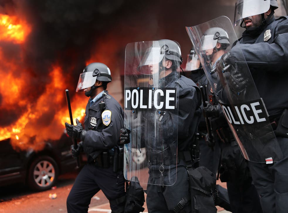 Police in riot gear move towards demonstrators in downtown Washington DC after a limousine was set on fire during Donald Trump's inauguration.