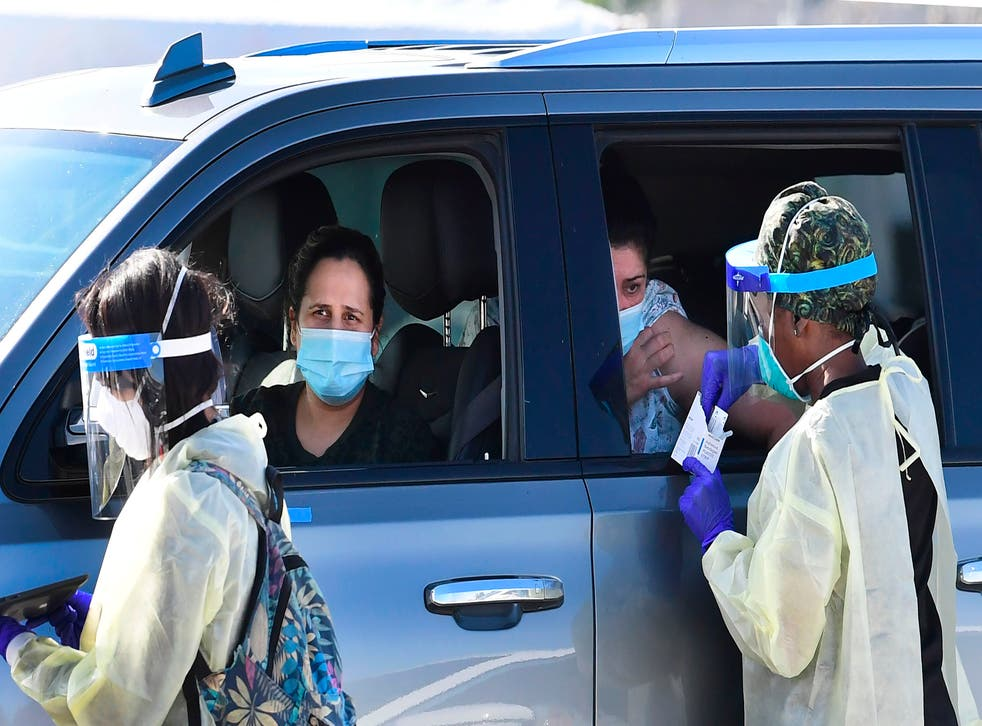 <p>People pull up in their vehicles for Covid-19 vaccines in the parking lot of The Forum in Inglewood, California</p>