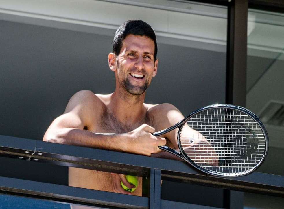 <p>Novak Djokovic smiles at fans from a hotel balcony in Adelaide</p>