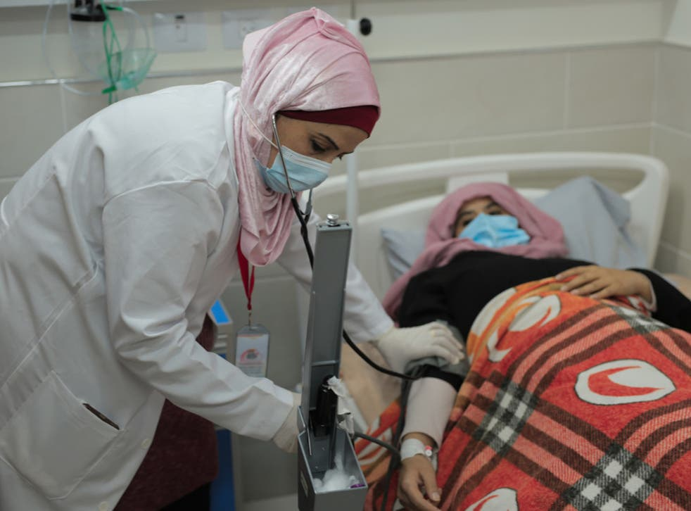 Nurse Heba Shalan from the Gaza Strip says she is often paid less than her full salary; Oxfam says women have been hit harder by the crisis