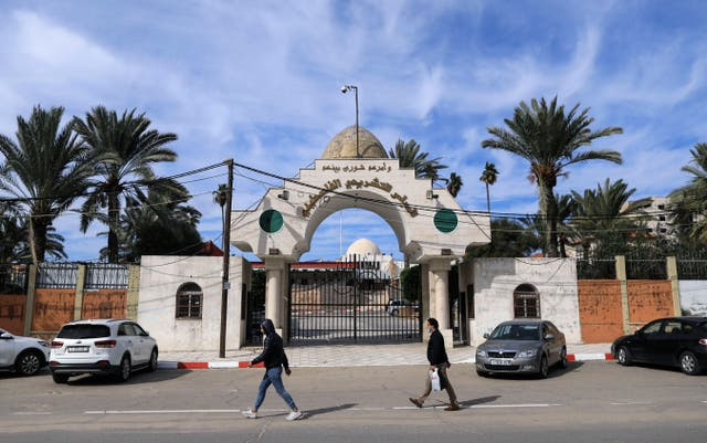 Palestinians walk past the entrance of the Legislative Council building in Gaza City, on 17 January, 2021. The UN has called on Israel to swiftly provide vaccines to Palestinians living in occupied territories.
