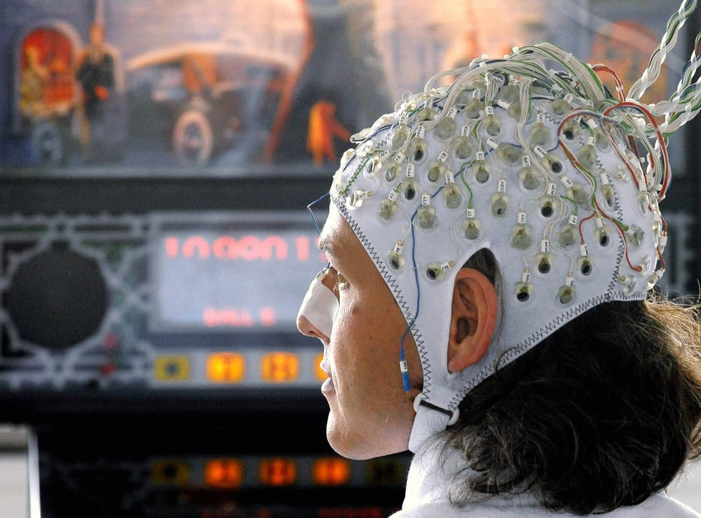 A researcher operates a pinball machine via electrodes attached to his head in an early demonstration of brain-computer interface technology on 4 June, 2009 in Berlin