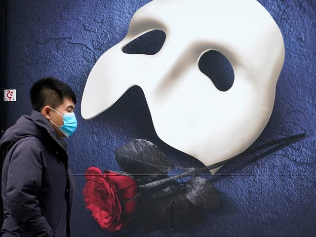 A man wears a face mask as he walks pasta a Phantom of the Opera poster in Manchester