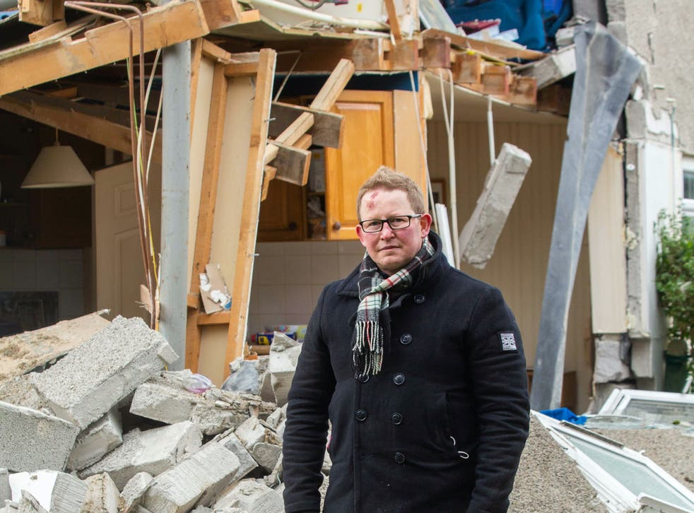 <p>Darren Cornish outside his parents' ruined home in Bude </p>