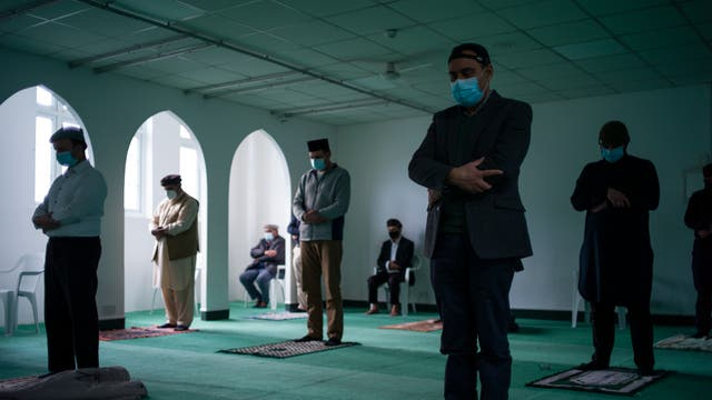 Members of the Ahmadiyya Muslim Community take part in Friday prayers at the Baitus Subhan Mosque in Croydon, England. For nearly the past year, the Covid-19 pandemic, and its resulting limits on public gatherings, have forced religious communities to find new ways to observe prayers, with many events being marked at home. Mosques as well as other places of religious worship remain open, though numbers have been limited to help maintain social distancing