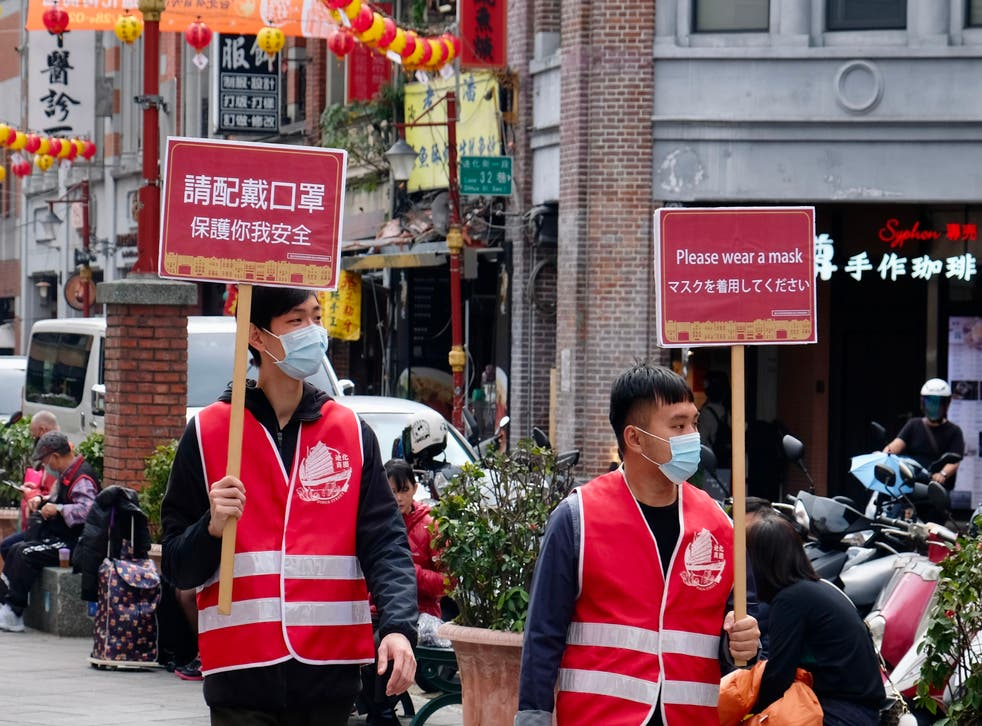 <p>File: Two volunteers walk around the Dihua traditional market with signs calling for people to wear masks in Taipei on Tuesday</p>