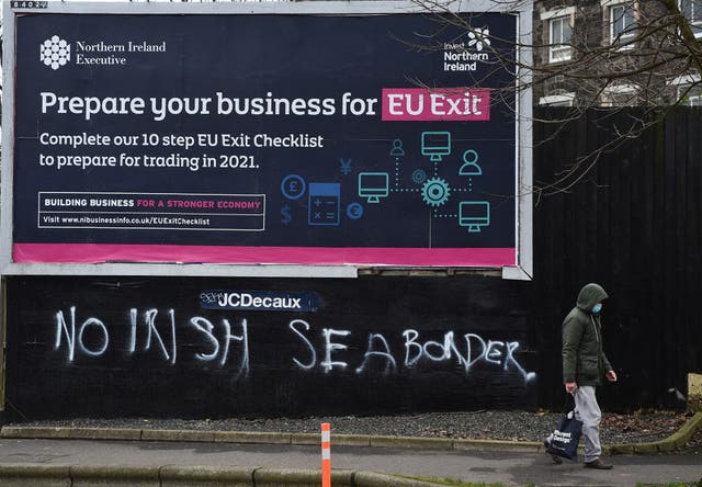 A man walks past graffiti in the loyalist Sandy row area, which reads 'No Irish sea border' under an EU Exit billboard on 30 January, 2021 in Belfast. The Police Service of Northern Ireland has been monitoring growing unionist discontent regarding the implementation of a so called Irish sea border