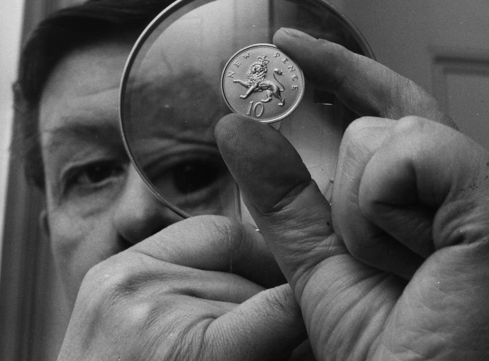 <p>Christopher Ironside, designer of the reverse side of the decimal 10 pence piece, examines the coin through a magnifying glass at the Royal Mint in 1968</p>