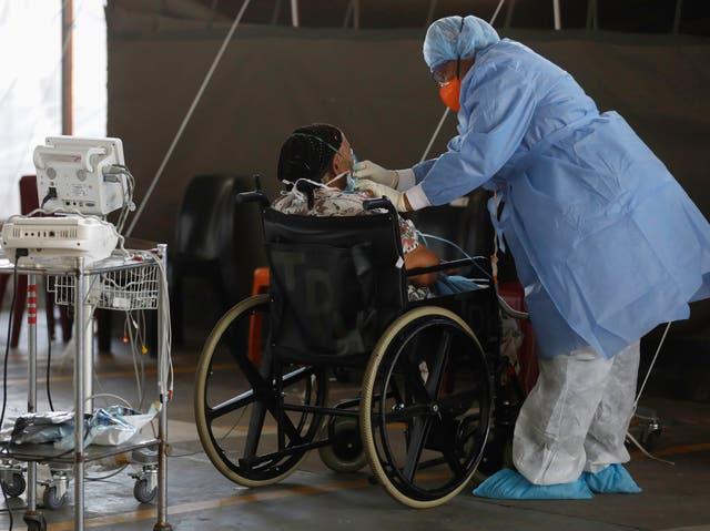 <p>Un trabajador de la salud que usa equipo de protección personal (EPP) se encuentra junto a un paciente en las salas temporales dedicadas al tratamiento de posibles pacientes con coronavirus COVID-19 en el Hospital Académico Steve Biko en Pretoria, Sudáfrica, el 19 de enero de 2021. Ministro de Salud, Dr. Zweli Mkhize declaró que se confirmaron 9.010 casos nuevos en las últimas 24 horas y que el total nacional ahora es de 1.346.936. </p>