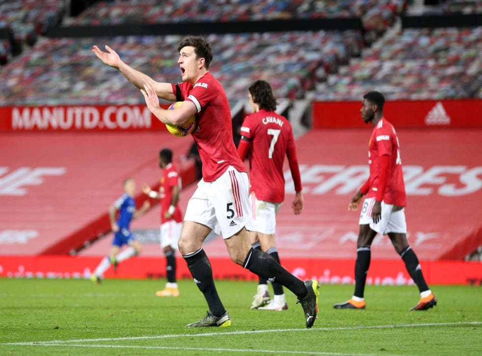 Harry Maguire gestures to the assistant referee for a handball decision after Everton's third goal