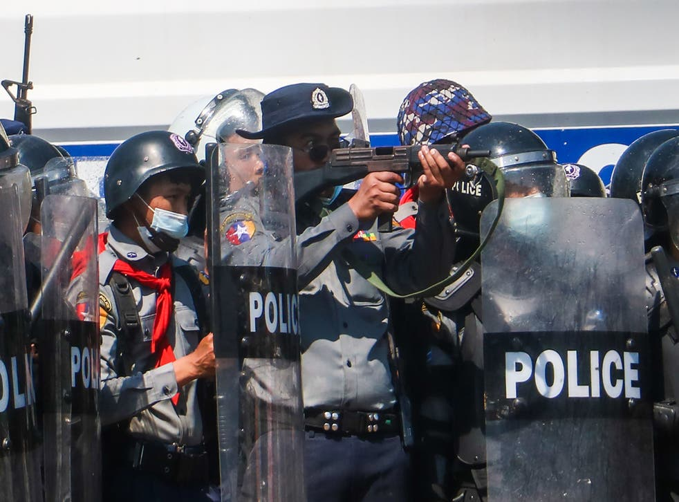 A police officer in Naypyidaw aims a gun during clashes with protesters taking part in a demonstration against a military coup in Myanmar
