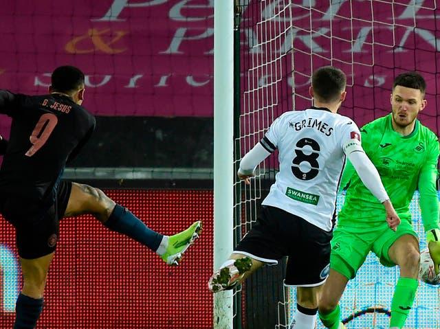 <p>El delantero brasileño del Manchester City Gabriel Jesus (L) anota el tercer gol de su equipo durante el partido de fútbol de la quinta ronda de la Copa FA inglesa entre Swansea y Manchester City en el Liberty Stadium de Swansea, Gales, el 10 de febrero de 2021 </p>
