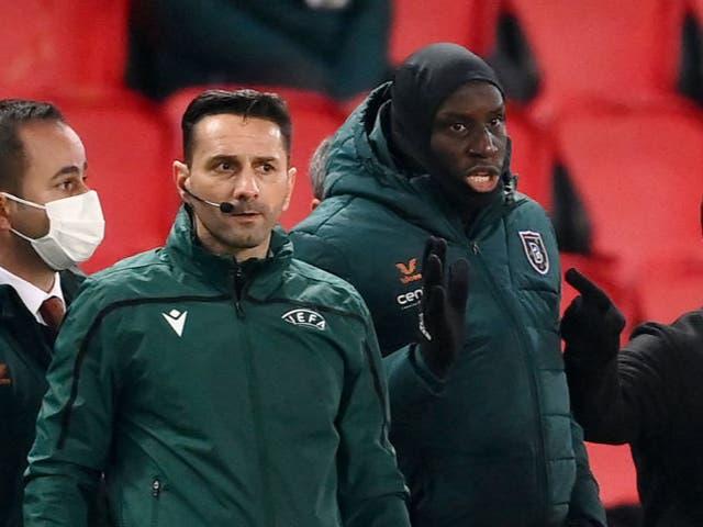 El cuarto árbitro rumano Sebastian Coltescu junto al delantero del Istanbul Basaksehir Demba Ba