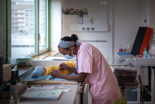 <p>A midwife attends to a newborn baby at a hospital in Saint-Denis, Paris, in February </p>