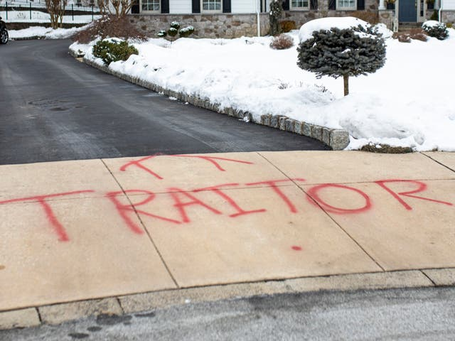 <p>Graffiti is spray painted on the driveway outside of attorney Michael van der Veen's suburban Philadelphia home, Saturday on 13 February 2021</p>