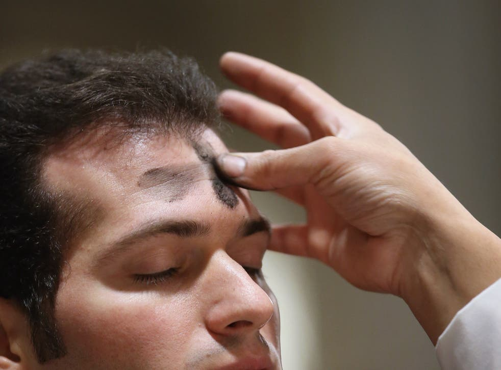 A Catholic receives ashes on his forehead while celebrating Ash Wednesday