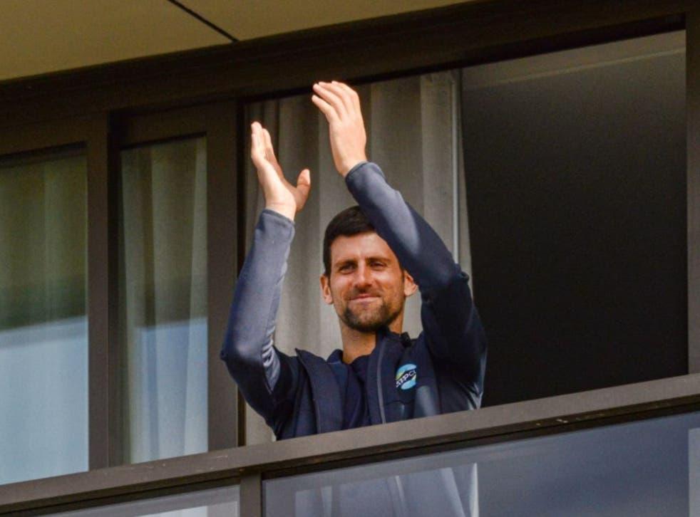 <p>Novak Djokovic gestures from his hotel balcony</p>