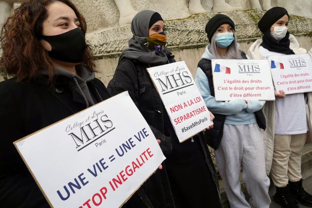 Activists hold placards reading 'No to the separatism law' in the center, and 'Equality of rights is the right of everyone to be different' on the right, during a gathering in Paris on Sunday