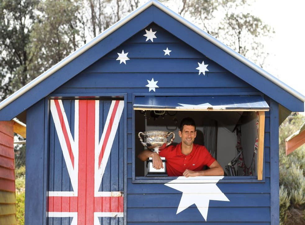 <p>Novak Djokovic poses with the Norman Brookes Challenge Cup trophy on Brighton Beach in Melbourne</p>