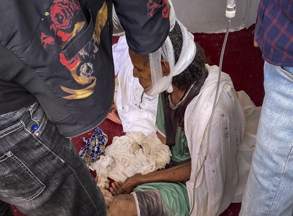 <p>An elderly woman who fled to the city of Axum in the Tigray region of Ethiopia to seek safety sits with her head bandaged after being wounded during an attack on the city  </p>