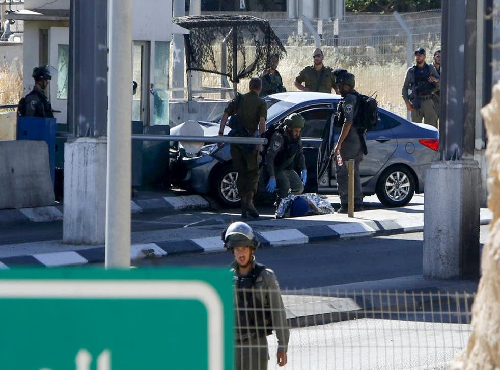 <p>Israeli forces cover the body of Ahmed Erekat</p>