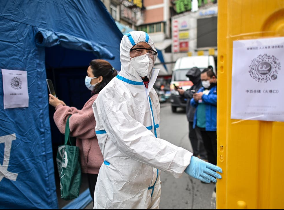 <p>A man wearing a protective suit controls the access to a market in Wuhan in March 2020</p>
