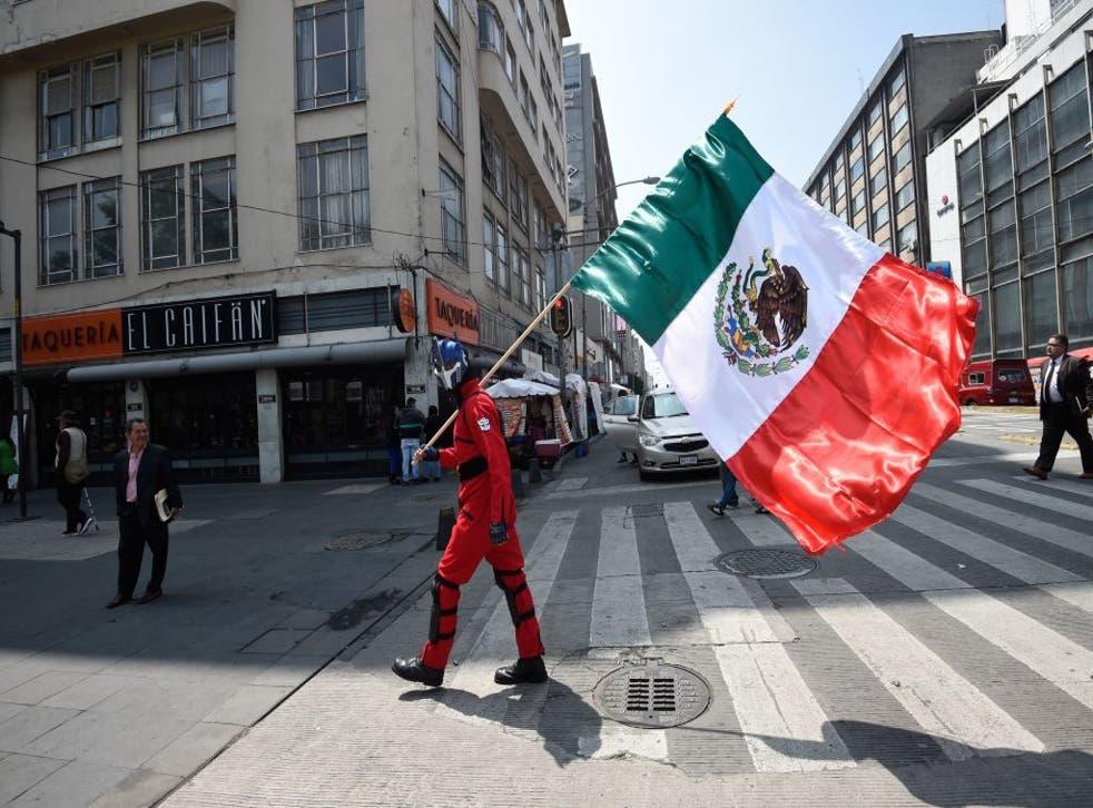 <p>Man waves Mexican flag.</p>