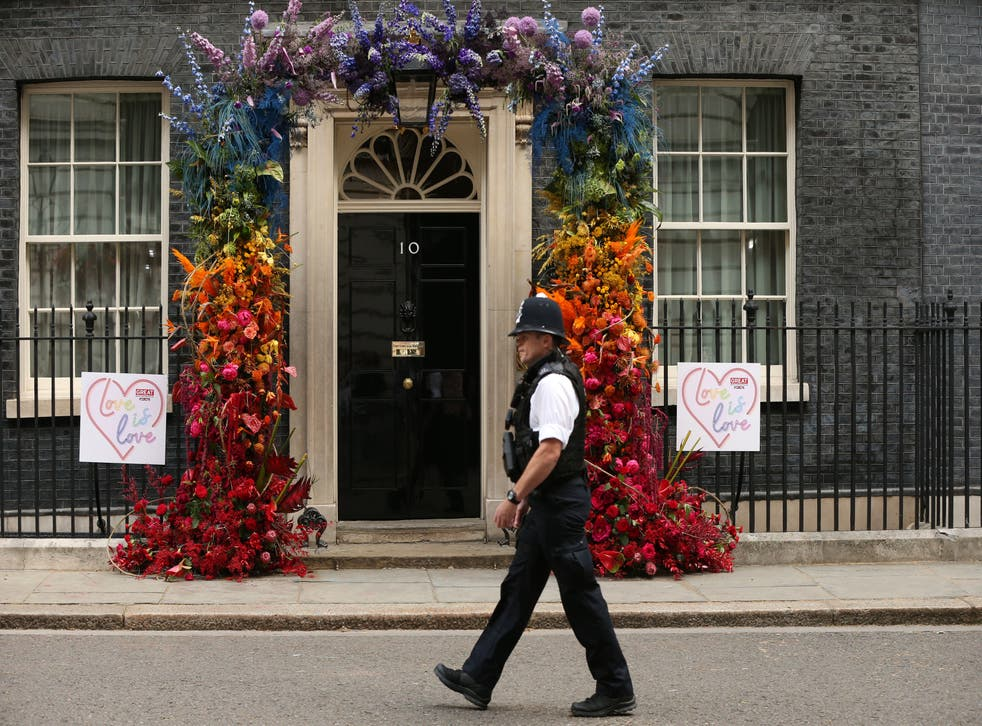 A police man walks past a floral LGBT+ decoration outside 10 Downing Street after a Pride reception held by the former prime minister, Theresa May in 2019