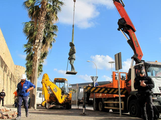 A crane removes the statue of Franco located in front of the wall of Melilla's old town