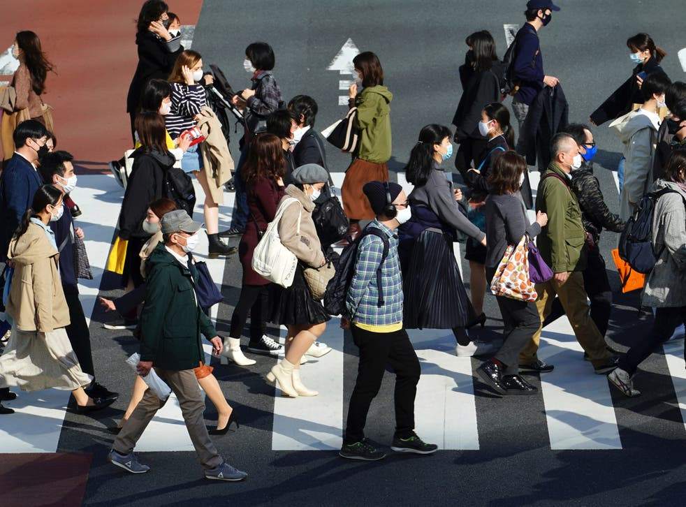 People wearing protective masks to help curb the spread of the coronavirus walk at a pedestrian crossing in Tokyo