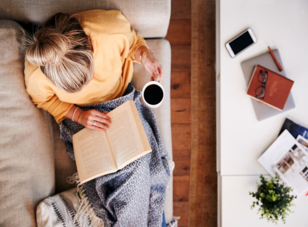 woman having a coffee and reading a book