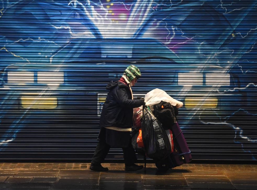 <p>A rough sleeper pushes their belongings past a Back to the Future mural in London on 13 December</p>