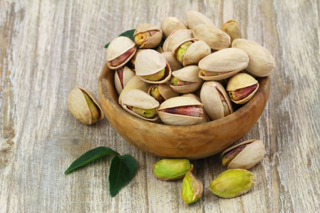 Pistachios in wooden bowl with copy space