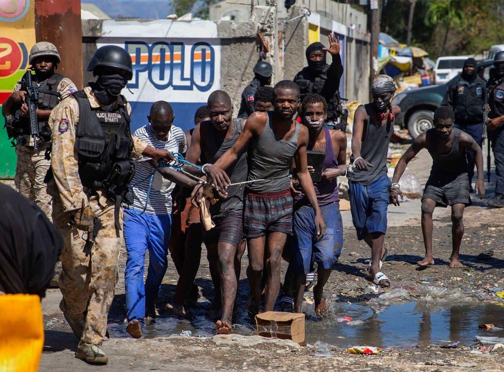 <p>Recaptured inmates led by police outside the Croix-des-Bouquets Civil Prison</p>