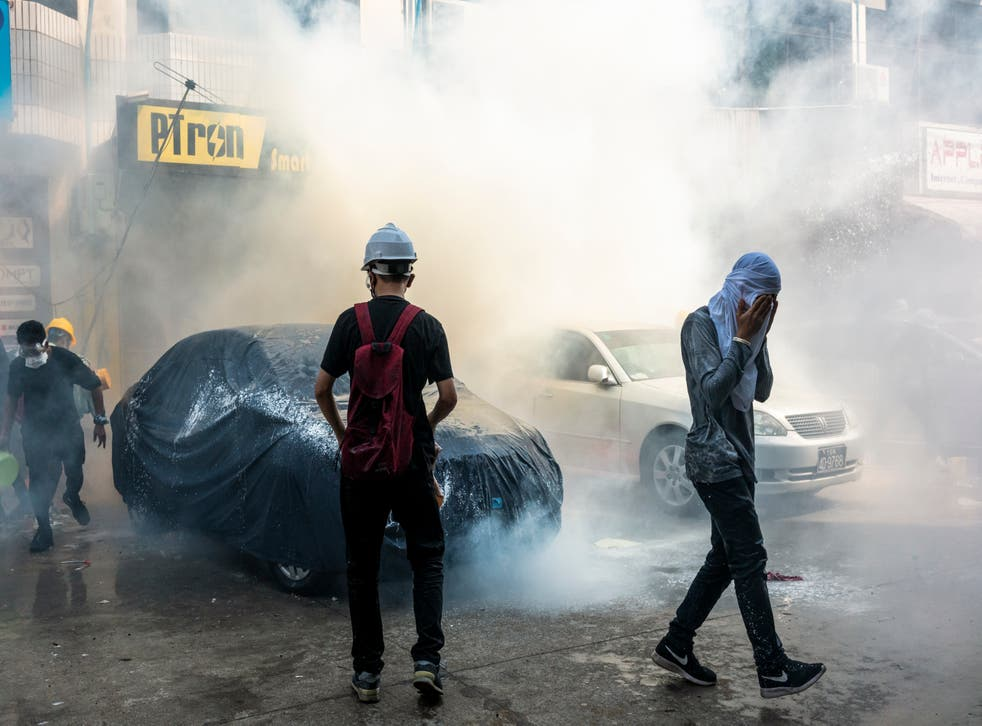 Protesters attempt to put out a tear gas canister fired by riot police