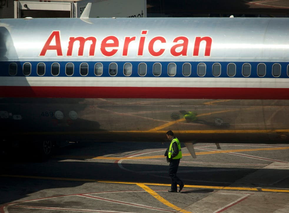 An airport worker walks past an American Airlines Inc. plane standing at a gate at LaGuardia Airport in the Queens borough of New York, U.S., on Monday, April 25, 2011. American Airlines Inc. is trying to grab market share in New York, the biggest and possibly most-contested U.S. aviation market, with terminal upgrades at LaGuardia Airport. Delta Air Lines Inc.'s bid to redo its space remains in limbo, bogged down in talks with federal regulators and US Airways Group Inc. about access to more landing rights. Photographer: Michael Nagle/Bloomberg