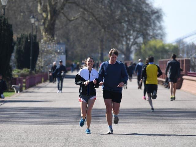 Joggers run through Battersea Park, London