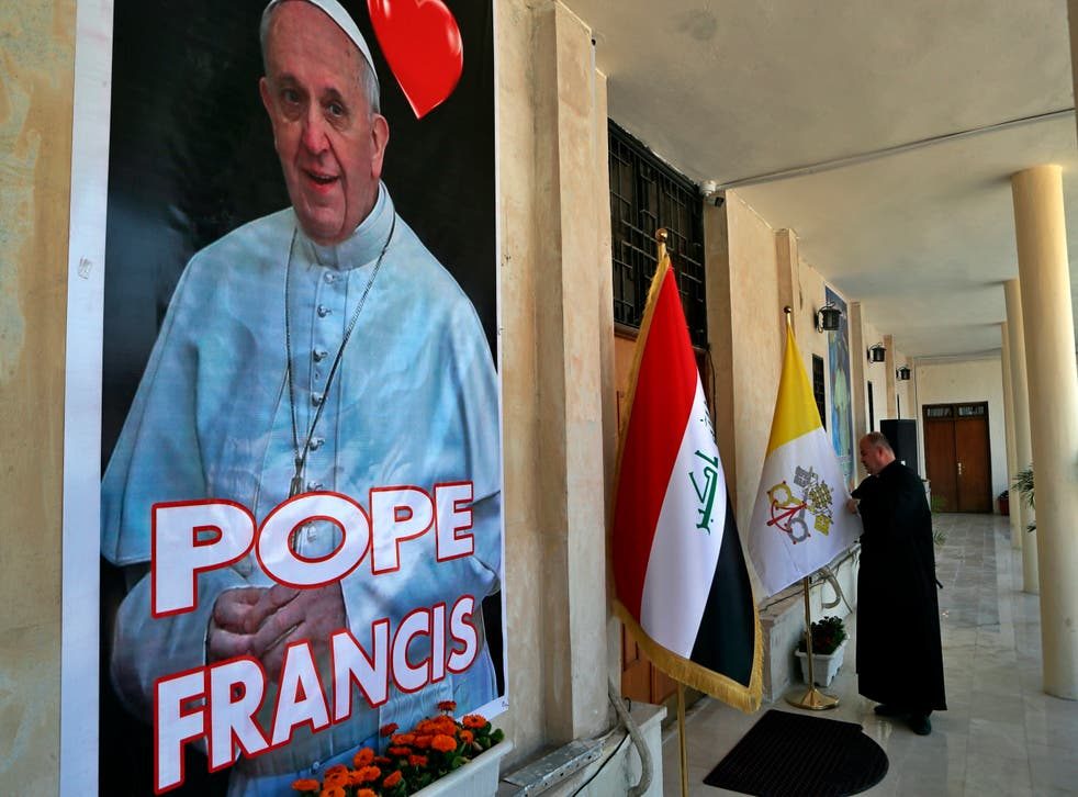 <p>Father Nazeer Dako arranges a Vatican flag to welcome Pope Francis at St Joseph's Chaldean Church in Baghdad</p>
