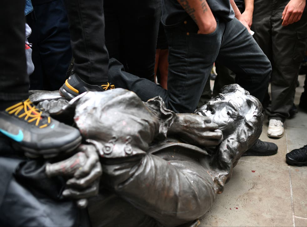 The Edward Colston statue at the feet of protesters after it was pulled down during a Black Lives Matter rally