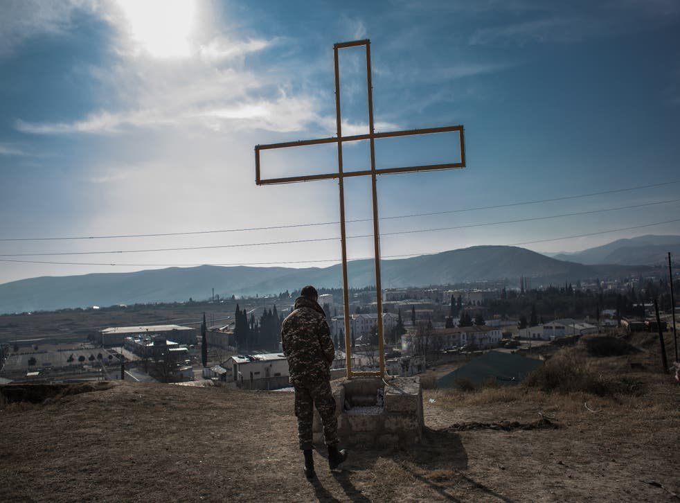 <p>An Armenian soldier prays in front of a cross at a military position in Martakert in Nagorno-Karabakh on 17 January</p>