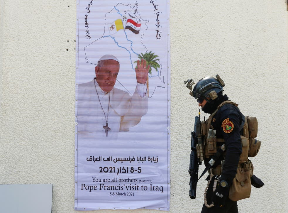 A security man walks near a poster of Pope Francis upon his upcoming visit to Iraq, in Baghdad