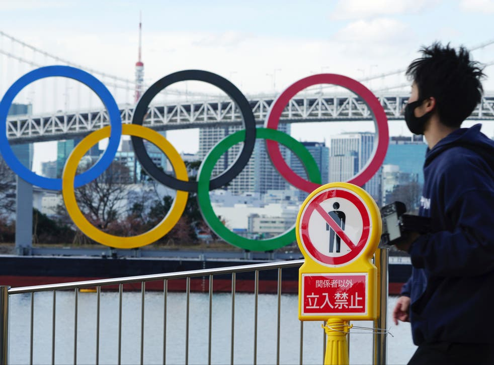 A man wearing a protective face mask walks near the Olympic rings
