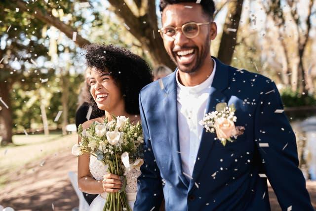 <p>Foto de una joven pareja de recién casados feliz recibiendo una lluvia de confeti al aire libre el día de su boda.</p>