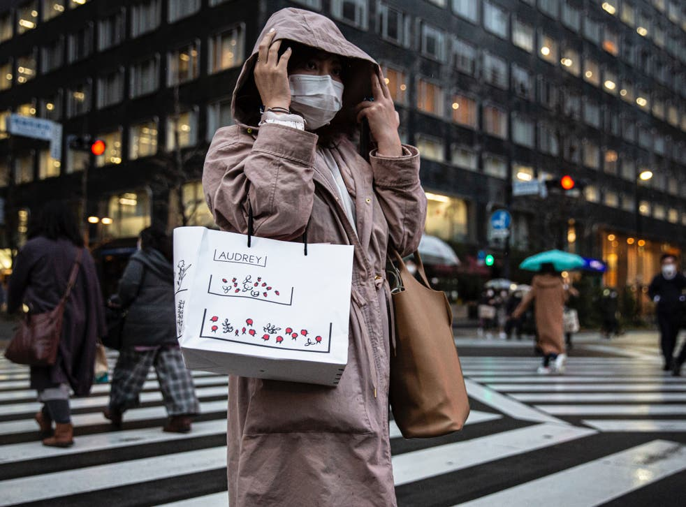 <p>File: A woman wearing a face mask crosses a road on in Tokyo</p>